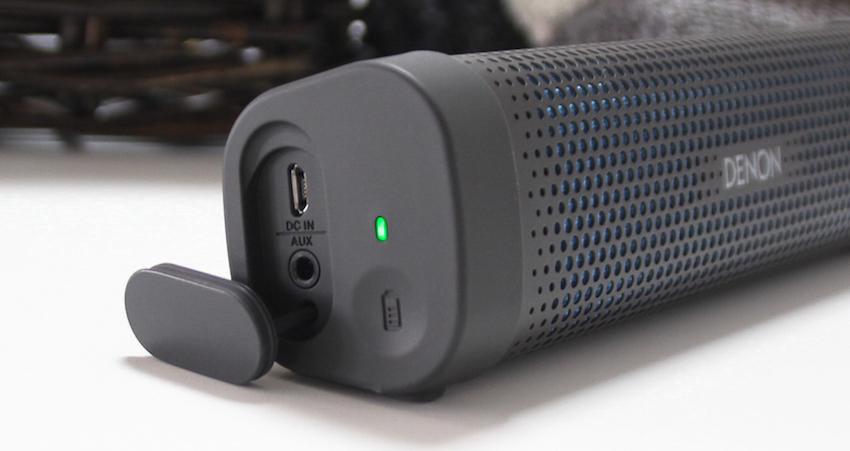 Hinter einer Staubschutzkappe in der linken Seitenwand finden sich Mini-USB- und Aux-Buchse. Gleich daneben die Batterieanzeige.
