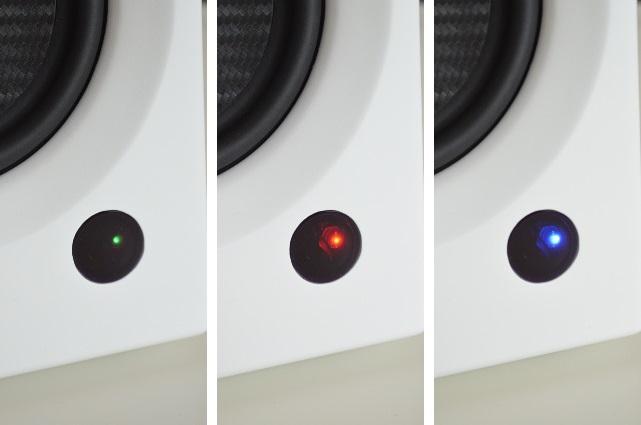 Die Farben stehen für die gewählte Quelle (Grün = analog, Rot = digital, Blau = Bluetooth), die Leuchtstärke informiert über An oder Aus.