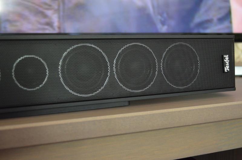 Die Mittel- und der Hochtöner schimmern deutlich sichtbar durch das Frontgitter hindurch. Das Herstellerlogo (rechts) haftet übrigens magnetisch und kann daher auf Wunsch auch horizontal platziert werden.