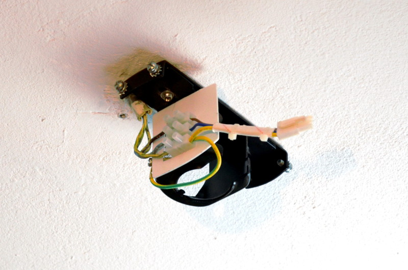 Die Deckenhalterung des Ventilators wird in der Nähe zum Stromkabel befestigt, das danach an den Klemmen Anschluss findet.