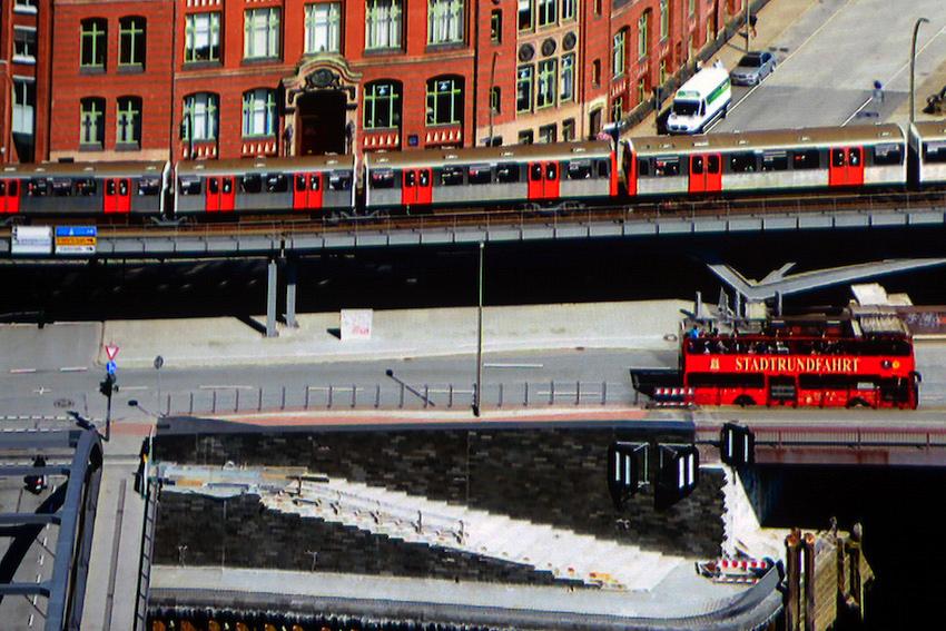 In dieser Ausschnittsvergrößerung einer Panoramaaufnahme von Hamburg, die ich aus der 21. Etage geschossen habe, zeigt der Sony VPL-VW520 auf der Alphaluxx Barium Ultra 8K jedes noch so kleine Detail. Die Schriftzug STADTRUNDFAHRT auf dem roten Doppeldecker wird perfekt abgebildet. Sogar die schwarzen Dichtungsgummis an den orangefarbenen U-Bahn-Türen sind zu sehen.  Foto: Michael B. Rehders