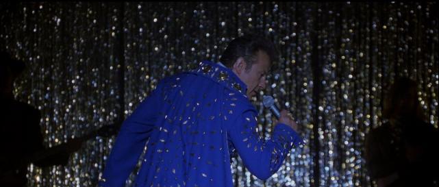 """Als sein Mitfahrer dann auch noch selbst die Bühne betritt, gerät Byron ins Grübeln, ob er vielleicht tatsächlich den echten """"King"""" aufgegabelt hat... (© Concorde Home Entertainment)"""
