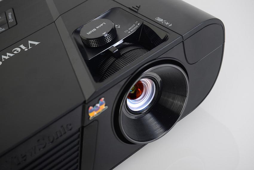Der große Lens-Shift-Regler erlaubt eine präzise Höhenverstellung des Bildes auf der Leinwand. Direkt davor befinden sich die Zoom- und Fokus-Regelungen. Damit lassen sich die Bildgröße und die Schärfe punktgenau einstellen. Rechts daneben: die Klappe für den WLAN-Dongle. Vollkommen unsichtbar verrichtet dieser darunter seine Tätigkeit. Foto: Michael B. Rehders