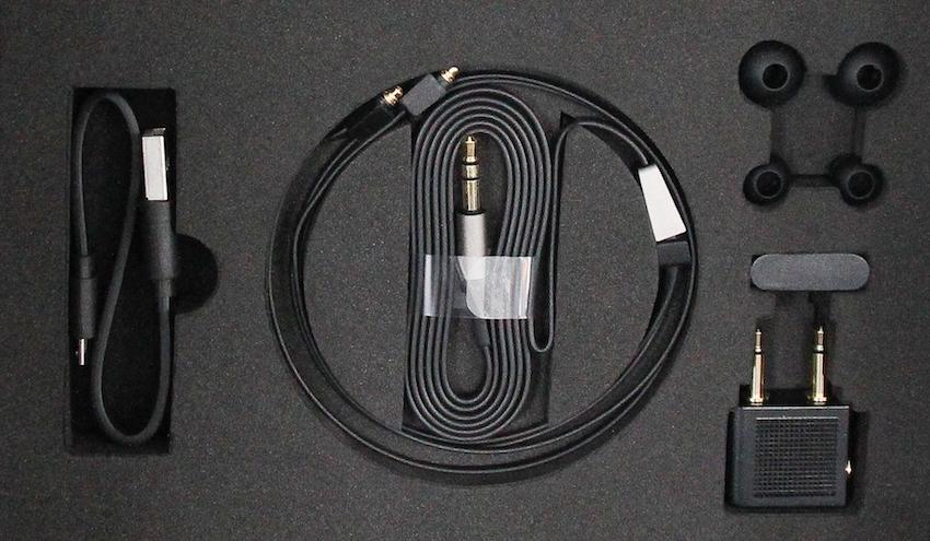 Neben dem obligatorischen Ladekabel gehören ein Signalleiter, weitere Ear-Tips, eine Kleiderklammer und ein Flugzeugadapter zum Lieferumfang des Motion One.