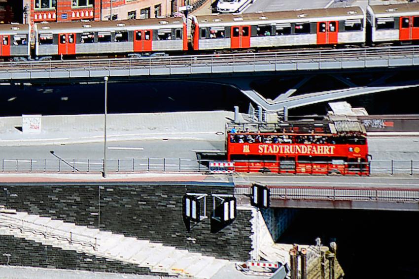 """BenQ W11000 - Original Screenshot (Makroaufnahme) eines 5-Prozent-Bildausschnittes desselben projizierten Bildes - nur diesmal vom W11000 wiedergegeben. Feinste Details werden vom Projektor perfekt herausgearbeitet. Der Schriftzug """"STADTRUNDFAHRT"""" weist aber auch jedes noch so kleine Detail auf, das auf der Original-4K-Fotoaufnahme vorhanden ist. Links neben dem Schriftzug ist das Hamburg-Wappen jetzt vollständig präsent. Darunter sind die dunklen Mauersteine klar und deutlich zu erkennen. Insgesamt erscheint das Bild sehr viel klarer und plastischer. Egal, ob es sich um die Lichteffekte auf der Metallblende an der U-Bahn handelt, dem grauen Straßenbelag oder um den vollständig abgebildeten Zaun auf der Brücke, der W11000 projiziert augenscheinlich jegliche Bildinformationen des Quellmaterials. Näher ist in unseren Tests noch kein Projektor an das Original-Foto heran gekommen."""