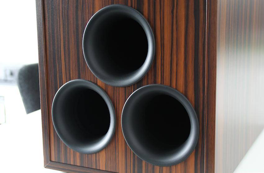 Rückseitig befinden sich die Öffnungen der drei Bassreflexrohre. Für einen optimalen Sound empfiehlt es sich einen entsprechenden Abstand zur Rückwand einzuhalten.