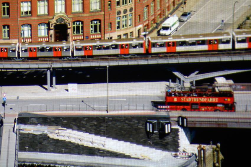 """Das Panaoramafoto von Hamburg wird vom ViewSonic PJD7720HD knackscharf und detailreich projiziert. In der Ausschnittsvergrößerung (siehe Screenshot) wird der graue Asphalt unverfärbt dargestellt. Die einzelnen weißen Treppenstufen werden klar und deutlich abgebildet, und das Rot des Doppeldeckers erscheint wie im Original. Der Schriftzug """"STADTRUNDFAHRT"""" wird nahezu vollständig abgebildet. Foto: Michael B. Rehders (Originalaufnahme und Screenshot)"""