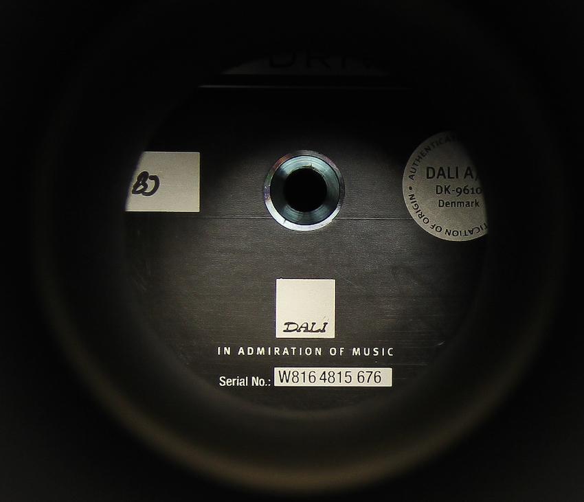 Tiefer Blick in die Box: Wer in den oberen Bassreflexkanal hineinschaut, sieht direkt die Rückseite des ersten Tiefmitteltöners. Die Prüfer-Paraffe links dokumentiert, dass dieser Speaker eine Qualitätskontrolle durchlaufen hat.