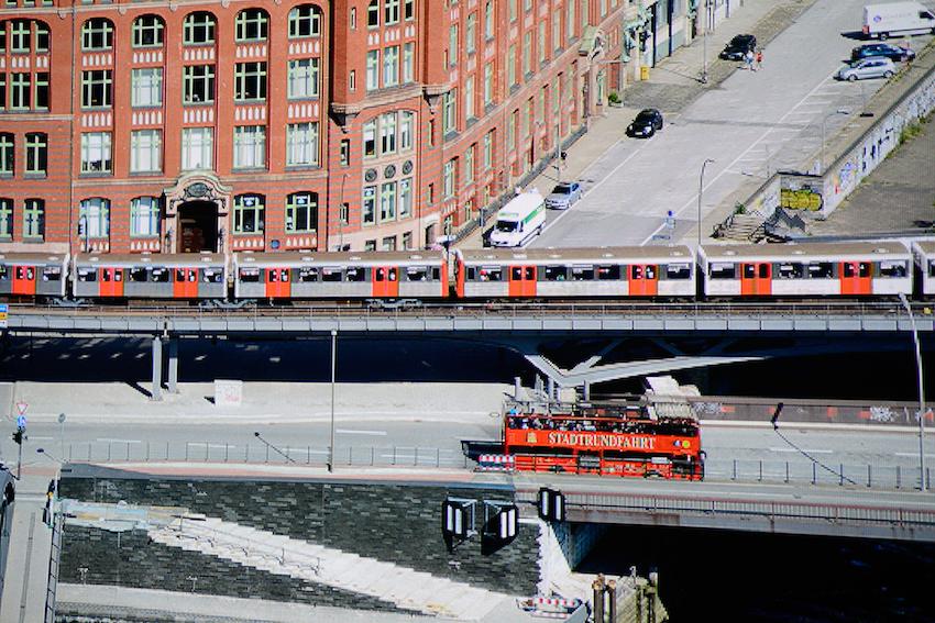 Die Panoramaaufnahme von Hamburg habe ich aus der 20. Etage des Hanseatic Trade Centers im Columbus Haus fotografiert. Dieser Screenshot ist ein 5 Prozent kleiner Ausschnitt davon. Die herausragende Schärfe und die gute Farbdarstellung sind gut zu erkennen. Der Schriftzug STADTRUNDFAHRT wird vollständig vom BenQ W1090 reproduziert. Das Rot des Doppeldeckers wird ebenso natürlich wiedergegeben wie der graue Asphalt und die weißen Treppenstufen, die hinunter zum Wasser führen. Originalaufnahme: Michael B. Rehders