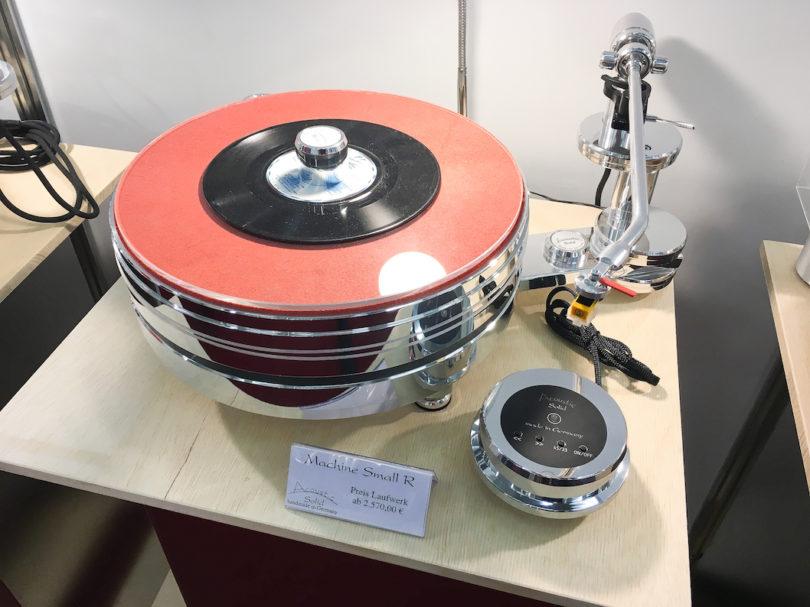u.a. den Machine Small R mit 50mm-Plattenteller, gefertigt aus massivem Alu und von einem Synchromotor im separaten Gehäuse angetrieben. Machine Small ist voll upgradefähig und zur Aufrüstung vorbereitet. Entkoppelt und höhenverstellbar über 3 Kegelspikes.