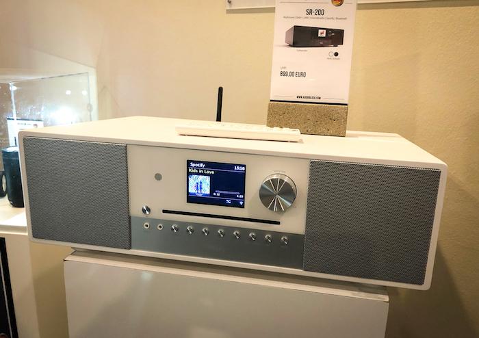 Gleich nebendran: das schicke Smart-Radio SR-100. Ein schickes FM-/DAB-Tischradio, das neben Netzwerkstreamung und Bluetooth auch gleich noch Multiroom-Fähigkeiten mitbringt.