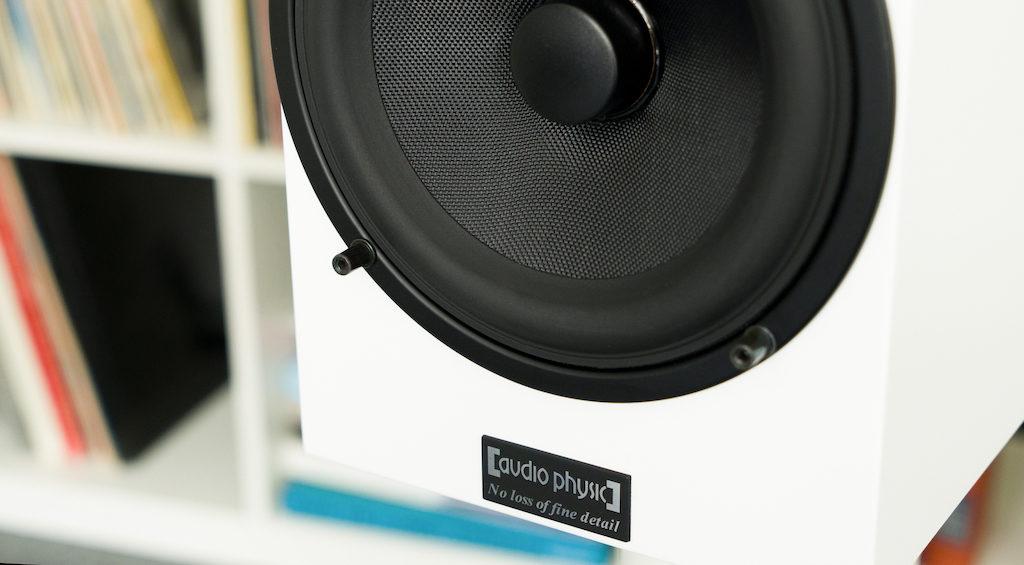 Die Schallwand wird nicht vollständig von der Frontblende bedeckt und das Herstellerlogo am unteren Rand bleibt stets sichtbar.