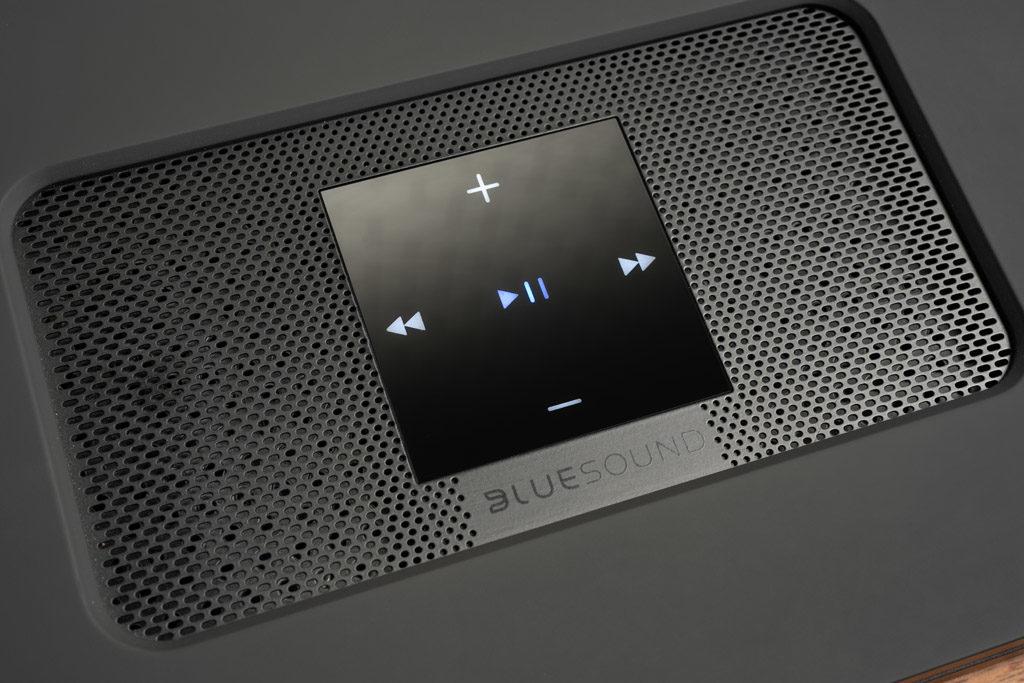 Auf einem schwarzen Gitter im Zentrum der Oberseite des Node 2i ist ein minimalistisches Steuerungs-Segment platziert.