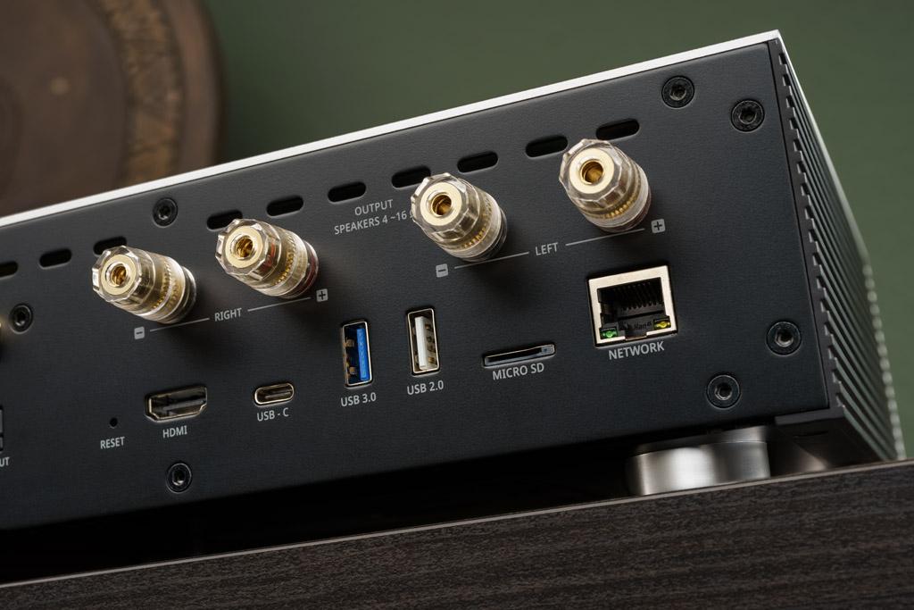 Die Anschluss-Sektion ist üppig: Hier sehen wir den HDMI Out zur Übertragen von Video-Inhalten auf einen Fernseher, zwei USB-A-Ports auf 2.0- und 3.0-Standard für Speichersticks, Festplatten oder ein CD-Laufwerk zum CD-Rippen, einen Slot für eine microSD-Karte und eine RJ45-Buchse für den kabelgebundenen LAN-Anschluss. Hinzu kommen die unsichtbaren Antennen für die Anbindung per WLAN, Bluetooth und AirPlay. Übernimmt der Rose RS201E allein die Amplifizierung, so gibt er das verstärkte Musiksignal über die vier vergoldeten Anschlussklemmen an ein Paar Lautsprecher ab. Die USB-C-Buchse für eine OTG (On The Go)-Verbindung dient nur Service-Zwecken.