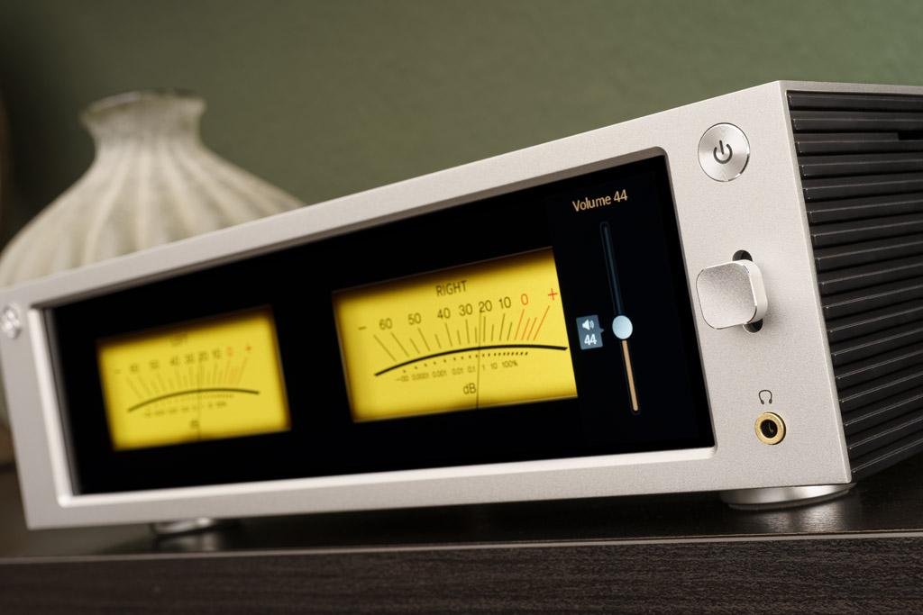 Außergewöhnlich: Die Lautstärkeveränderung kann man auch am Gerät vornehmen – mit einer Jog-Taste: Jedes Drücken nach oben oder unten sorgt für eine feinstufige Pegelveränderung, ein Druck auf diesen Taster aktiviert die Stummschaltung. Wer möchte, lässt sich den Pegel im Retro-Style als VU-Meter anzeigen – und das sieht dank der Qualität des Displays täuschend echt aus. Ansonsten bietet die superaufgeräumte Front nur noch den An/Standby-Taster als Bedienelement – und den Kopfhörereingang.