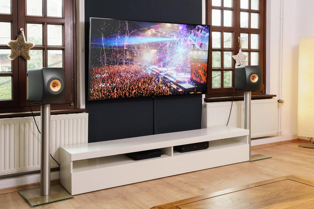 """Die LS50 Wireless II gibt auch den Film- und Fernsehton wieder – dank des HDMI eARC-Anschlusses. eARC steht für """"Enhanced Audio Return Channel"""", zu Deutsch: verbesserter Audiorückkanal. Er ermöglicht eine größere Bandbreite und Geschwindigkeit der Signalübertragung, so kann man den Ton selbst in Formaten wie DTS:X und Dolby Atmos genießen."""