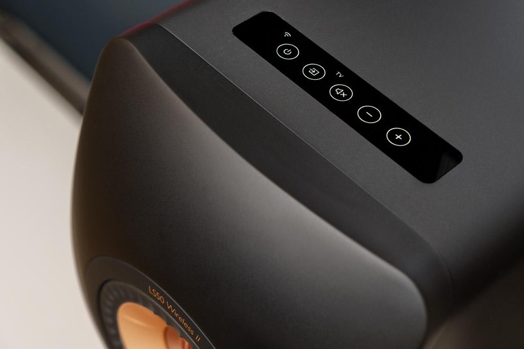 """Die perfekt eingelassene OLED-Anzeige gibt Auskunft über den aktuellen Betriebszustand und ermöglicht als sensitives Touch-Display zugleich die Nahbedienung ohne optisch störende Tasten. Über die gut reagierenden Sensorfelder lässt sich die LS50 Wireless II ein-, aus- und stummgeschalten, die Quelle anwählen und die Lautstärke verändern. Das WLAN-Symbol informiert uns, ob die Speaker mit dem Netzwerk verbunden sind. Streamen wir per Bluetooth, leuchtet das bekannte Blaubart-Symbol, und mit den Kürzeln """"TV"""", """"OPT"""", """"CX"""" und """"AUX"""" werden die anderen ausgewählte Zuspielwege angezeigt."""