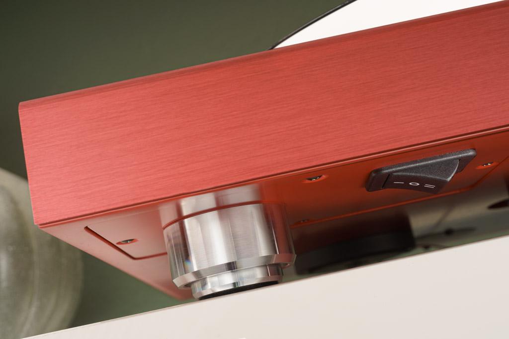 Die zweiteilige Fußkonstruktion birgt eine Federung, die interne wie externe Vibrationen wirkungsvoll absorbiert. Die Federung ist genau auf das Gewicht des Laufwerks abgestimmt. Der rechts sichtbare Schalter dient der Milderung oder Abschaltung der Tellerbeleuchtung.