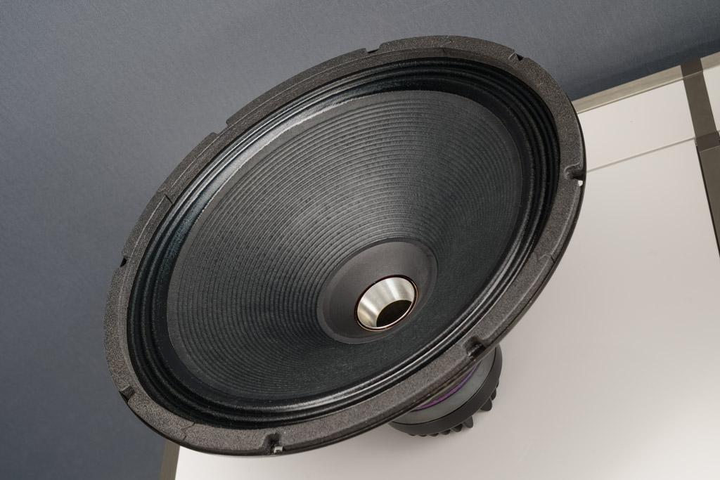 Hier ist das zuoberst sitzende Koaxial-Chassis ausgebaut und damit sichtbar: Die Höhen und Mitten bis 800 Hertz liefert ein Tweeter, der seinen Schall über einen Tunnel zentral durch den Antrieb des Woofer abstrahlt. Wir sehen das Ende dieses Tunnels, er mündet in eine zweiteilige Schallführung: Der silbermetallene Hornansatz ist dabei starr und fest, die schwarze Schallführung hingegen wurde auf die Konusmembran des Mitteltieftöners aufgeklebt. Dieses Präzisionsteil aus superleichtem und überaus steifem Polyamid wird von Mach One classics im 3D-Druck-Verfahren gefertigt.