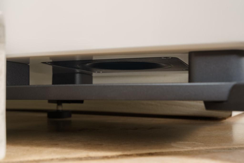 Im Sockel verborgen sitzt der untere Bassreflex-Port. Er führt die austretende Luft im Downfire-Modus gen Untergrund. Der Schall trifft auf die Bodenplatte des Sockels und wird von hier homogen in alle Richtungen zu den Seiten verteilt.