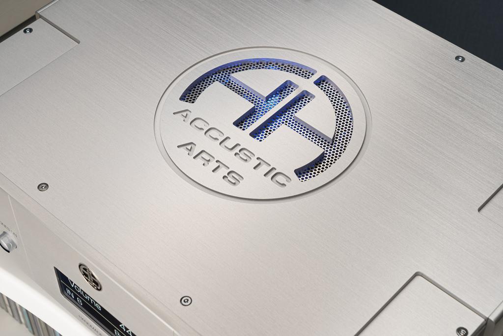 Auf der Oberseite dient das kunstvoll gefräste Logo auch der Ventilation der Elektronik. Sie kann man durch das geheimnisvolle blaue Glimmen, das durch das unterfütternde Lochgitter dringt, erahnen.