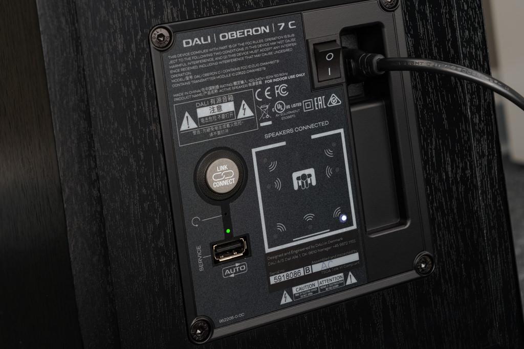 """Die Rückseite der Oberon 7 C: Neben der Buchse für den Netzstecker und dem An/Aus-Schalterbietet finden wir hier den """"Link Connect""""-Taster für die Paarung mit dem Hub. Welche Position der Lautsprecher einnehmen soll, definiert man mithilfe des Displays, das einen Hörraum in stilisierter Form zeigt: Der aktuell eingestellte Standort des Lautsprechers wird durch eine leuchtende LED angezeigt. Mit jedem Druck auf den """"Link Connect""""-Taster """"wandert"""" die Lautsprecher-Position weiter. Auf diesem Bild ist diese Oberon 7 C als linker Frontlautsprecher definiert."""
