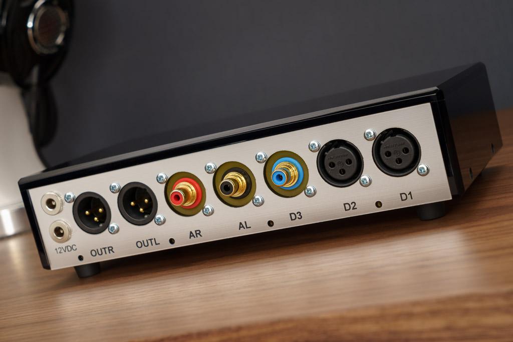 Die Anschlüsse des NOS-DAC 2: Eingangseitig bietet er analog einen quasi-symmetrischen Hochpegel-Input und digital drei Schnittstellen: D1 ist immer als AES/EBU-Input ausgelegt, D2 und D2 werden nach Wahl als AES/EBU- oder als S/PDIF-Eingang realisiert – und hier wiederum wahlweise als koaxiale Cinch-Buchse oder als klanglich überlegener BNC-Anschluss. Toslink ist nicht möglich, ein optisches S/PDIF-Signal kann aber mithilfe eines zusätzlichen Toslink/Coax-Konverters eingespeist werden. Ausgangsseitig bietet der NOS-DAC 2 einen symmetrischen Analog-Output zum Anschluss an eine Endstufe oder Aktivlautsprecher. Die beiden links außen positionierten Buchsen dienen der Spannungsversorgung. Über das externe Netzteil wird der DAC gespeist, über den Konverter dann aber auch der optionale Formatwandler/Reclocker, mit dessen Hilfe Files per USB zugespielt werden können.