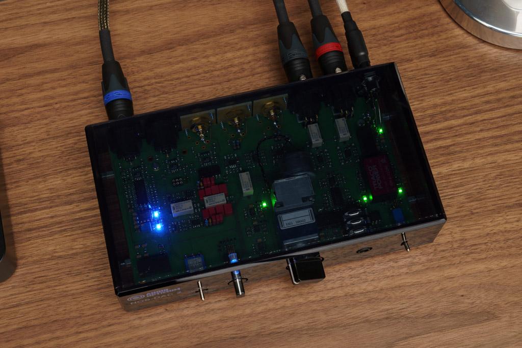 Der Konverter ist in ein Gehäuse aus getöntem Acryl gekleidet. So ist die Technik sichtbar – mitsamt den blau leuchtenden LED. Sie dienen eigentlich nicht der Optik, sondern stabilisieren mit ihrer besonders rauscharmen Fluss-Spannung die symmetrische Versorgung des Konverter-Chips TDA1543.