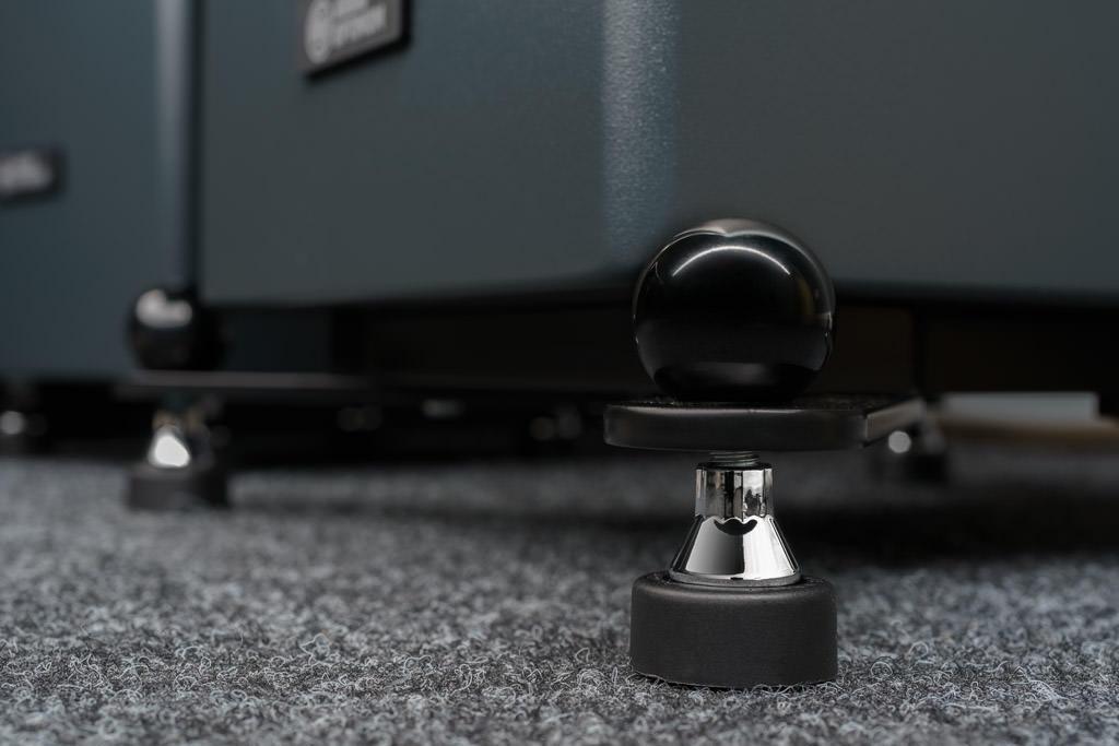Die Lautsprecher sind auf Auslegern gelagert. Dies erhöht die Standfestigkeit, befördert aber auch eine leichtere Anmutung: Das Gehäuse scheint zu schweben. Zur Minimierung von Vibrationen sitzt zwischen Korpus und Auslegern eine absorbierende Unterfütterung. Die Füße sind höhenverstellbar, die zierende oberseitig aufgeschraubte Kugel dient als fixierende Konterung. Bei den Füßen handelt es sich um die von Audio Optimum stets eingesetzten Soundcare Superspikes. Sie bewirken eine Entkopplung und passen sich unebenen Untergründen an.