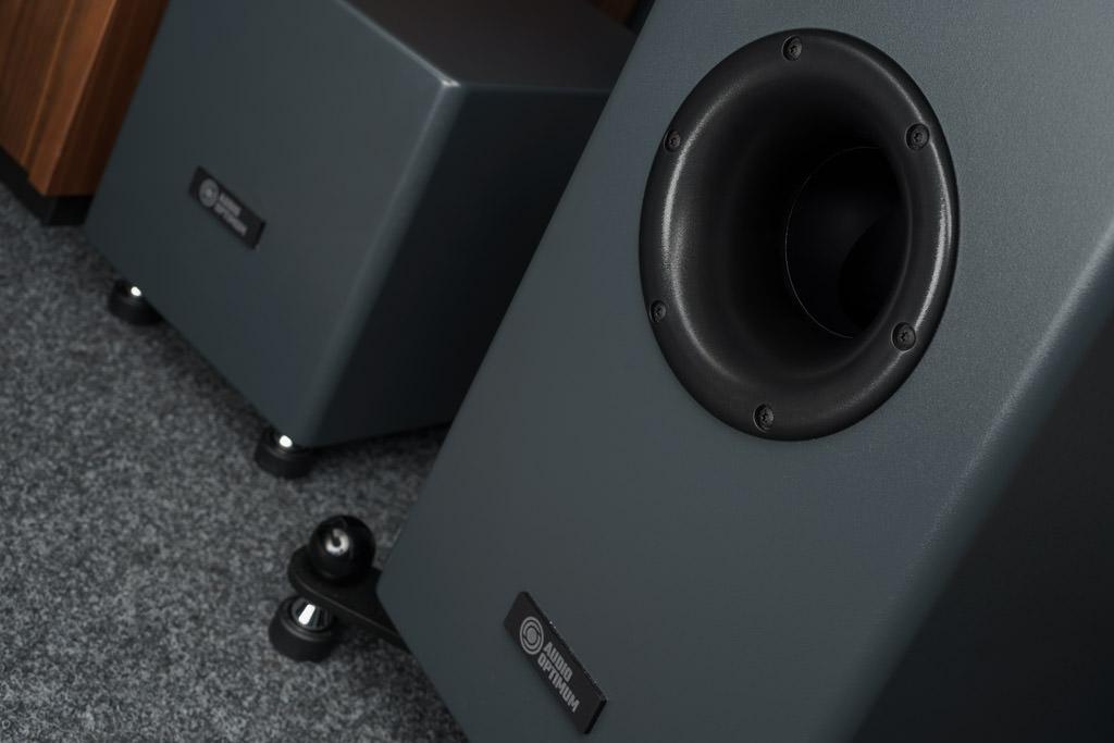 Der große Bassreflex-Port ist auf der Vorderseite des Lautsprechers positioniert. Seine Abrundung minimiert mögliche Luftströmungsgeräuschen. Das Rohr vollführt innerhalb des Gehäuses eine Krümmung um 90 Grad nach unten. Dadurch erzielt die Bassreflexabstimmung ihre maximale Effizienz. Durch die weite Entfernung vom Untergrund wird eine Schwingungsanregung des Boden verhindert.