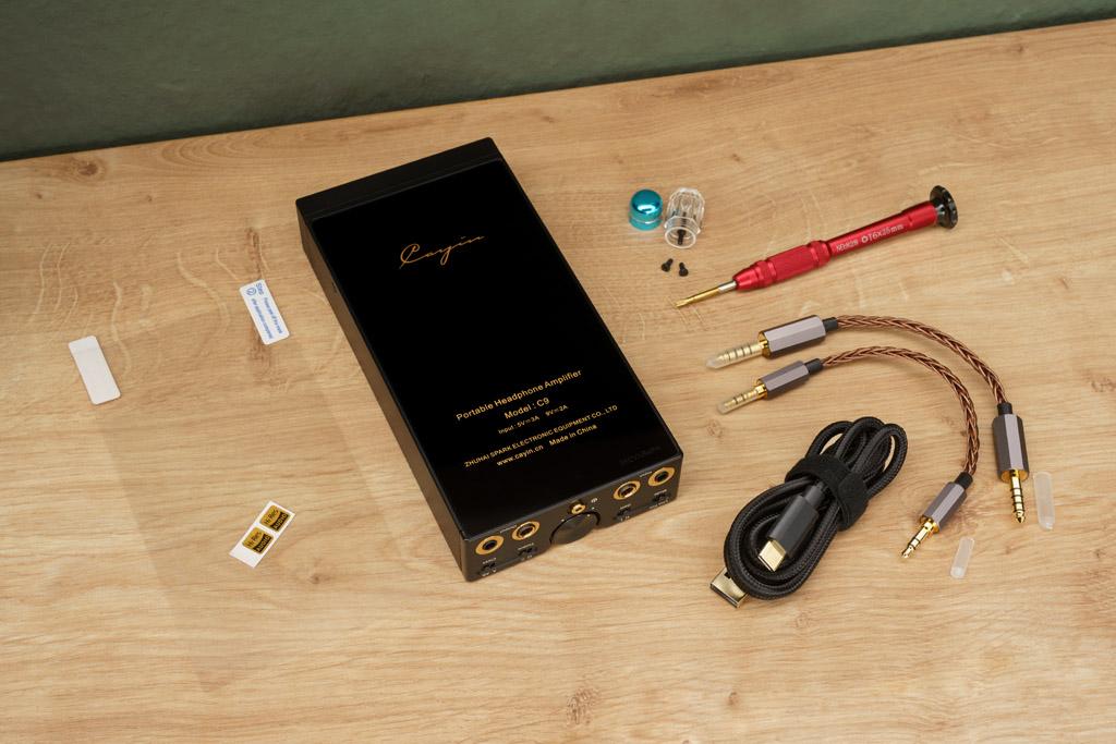 Der Cayin C 9 ist mit einigem Zubehör ausgestattet. In der attraktiven Pappschatulle, in der Verstärker geliefert wird, finden wir in der unteren Schublade eine Rückseiten-Schutzfolie, ein USB C/USB A-Ladekabel, ein symmetrisches und ein unsymmetrisches Adapterkabel, eine Phiole mit Ersatzschrauben zur Fixierung des Batteriemoduls und den dazu nötigen Schraubendreher. Ein Ladenetzteil würde den Lieferumfang abrunden.