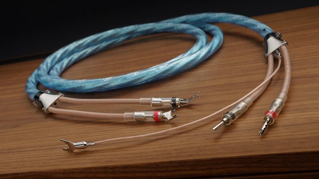 Das Supra Cables Sword Excalibur ist mit seiner eisblauen Anmutung klar als Kabel des schwedischen Traditionsunternehmens erkennbar. Durch sein dunkleres, teiltransparentes Design strahlt es aber eine leicht mythische Aura aus – und durch die metallenen Applikationen eine attraktive Noblesse.