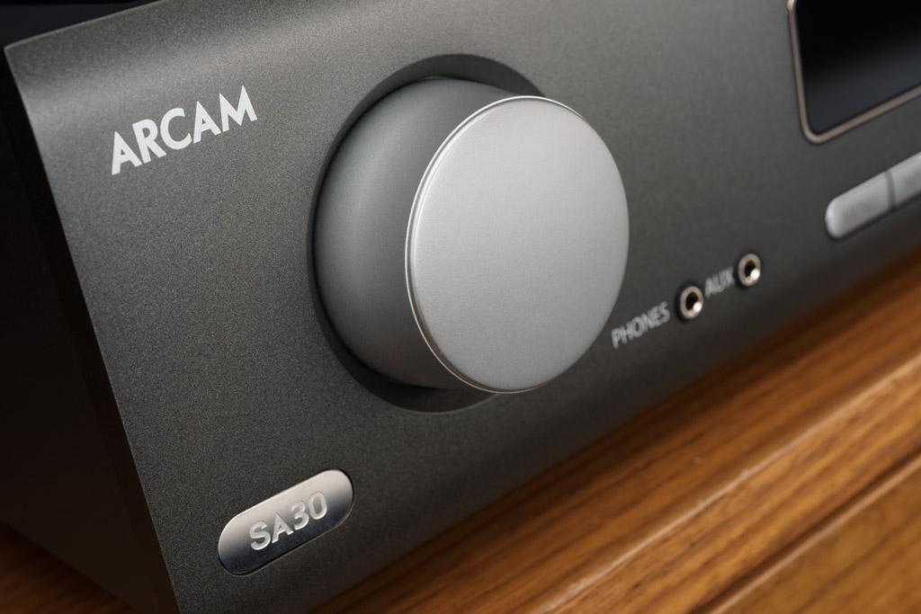 Der metallene Drehgeber ist mit einer Kunststoff-Kappe versehen und rotiert aufgrund zu großen Spiels unrund. Gängigkeit und Rastung des dahinter sitzenden Drehgebers sind hingegen sehr gut. Als Plus-Feature sind hier noch der Kopfhörerausgang und der Aux-Eingang für den schnellen Anschluss einer Audio-Quelle zu sehen.