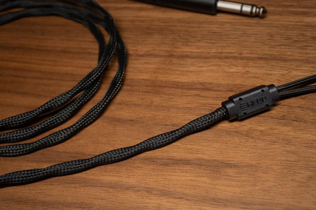 Das Anschlusskabel besitzt eine haptisch überaus angenehme Mantelung. Sie schirmt die Leiter effektiv gegen externe Einflüsse, zudem ist das Kabel auf minimierte Mikrofonie- und Übersprechungseffekte hin optimiert. Ab dem Splitter messen die einzelnen Leitungen für den Anschluss an die rechte und linke Muschel fast sechzig Zentimeter.