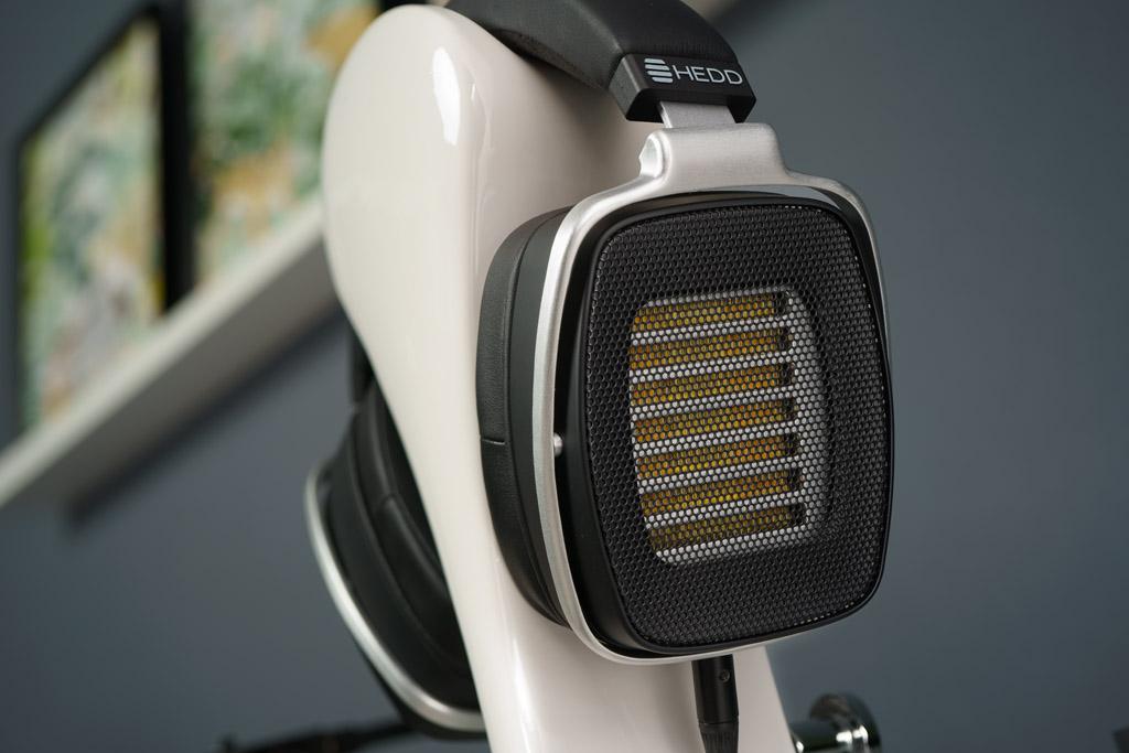 Der HEDDphone ist ein offener Kopfhörer. So sieht man durch das feine schwarze Gitter die gelbe Membran-Folie des Air Motion Transformers und die silberne Einfassung der Treibereinheit.