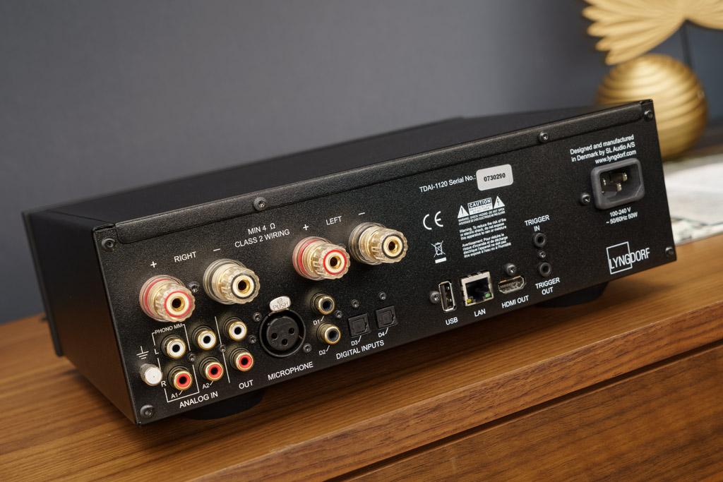 Die Anschluss-Sektion ist vielseitig: Unter den analogen und digitalen Schnittstellen fällt sofort der Phono-Eingang mit Erdungsklemme auf. Der Micophone-XLR-Input dient allein dem Anschluss des Einmessmikrofons. Über die Trigger-Buchsen lässt sich der Verstärker in Kopplung mit anderen Komponenten ein- und ausschalten. Antennen sehen wir hingegen glücklicherweise nicht: Sie sind unauffällig in dis Areal der Glasscheibe integriert worden.