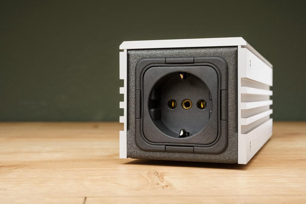 Der andere Steckplatz ist die bekannte Schuko-Steckdose. An sie wird eine nachfolgende Netzleiste oder ein Stromoptimierer angeschlossen, von dort aus werden dann die einzelnen Komponenten versorgt.