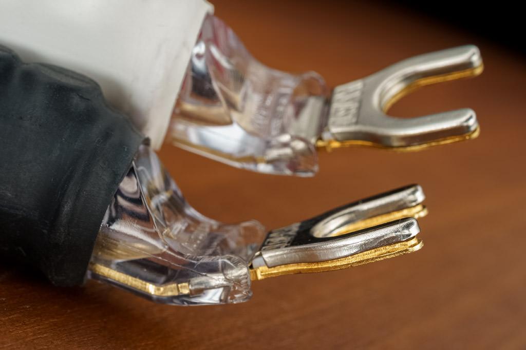 Die Gabeln der WBT nextgen Sandwich Spades besitzen einen aufwändigen Sandwich-Aufbau: zwischen dem Kofferteil aus Edelstahl und der signalleitenden Gabelteil aus nickelfrei vergoldetem Reinkupfer sitzt ein Elastomer als Schwingungsdämpfer. Er wan-delt Schwingungen in Wärme um und wirkt damit gegen Kontaktmikrofonie, Luft- und Körperschall. Zudem ermöglich er einen konstanten und hohen Kontaktdruck. Dabei stel-len vier geprägte Kontaktpunkte auf der Gabelunterseite einen genau definierten Kontakt her. Gemäß WBTs nextgen-Philosophie, nach der durch weniger Metalleinsatz auch we-niger Klangbeeinflussung stattfindet, ist auch bei diesem Gabelschuh das Leitermaterial auf ein Minimum reduziert und der Steckerkörper weitestgehend metallfrei konzipiert.